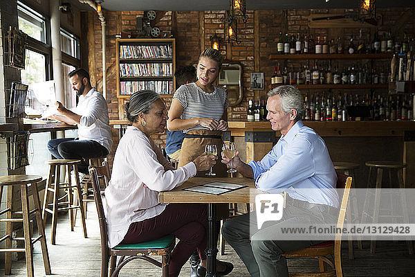 Kellnerin im Gespräch mit Kunden  die im Café sitzen