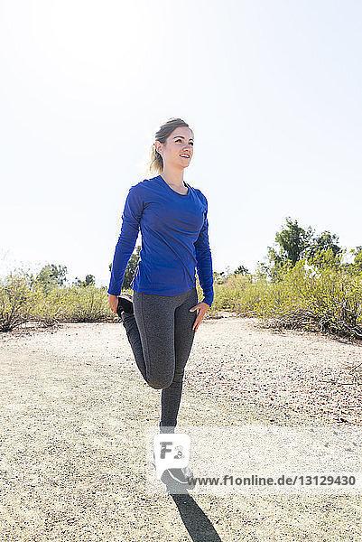 Wanderin trainiert im Stehen auf dem Feld vor klarem Himmel an einem sonnigen Tag