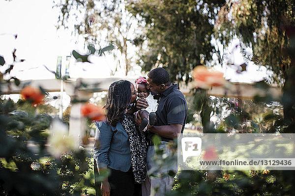 Eltern spielen mit der Tochter  während sie im Park stehen