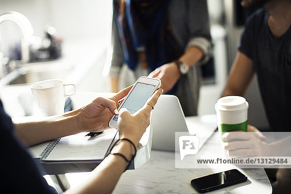 Geschnittene Frau benutzt Smartphone in Cafeteria