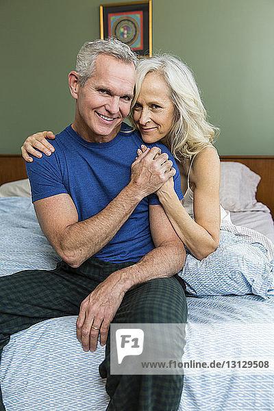 Porträt eines selbstbewussten Paares  das zu Hause auf dem Bett sitzt