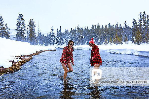 Freundinnen  die sich im Winter im See gegen den Himmel vergnügen