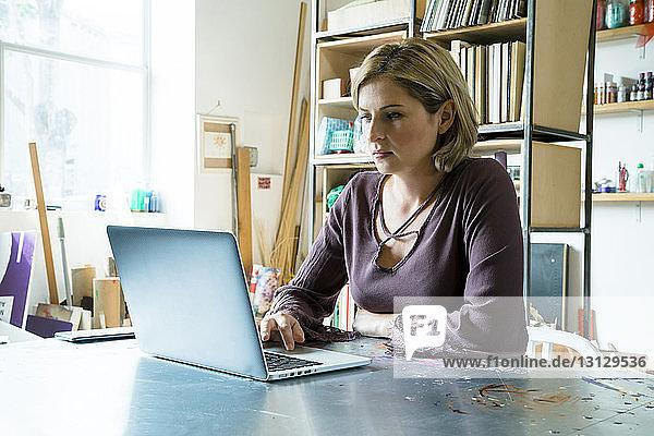 Geschäftsfrau benutzt Laptop-Computer bei der Arbeit im Büro