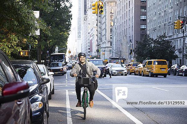 Happy man riding bicycle on city street