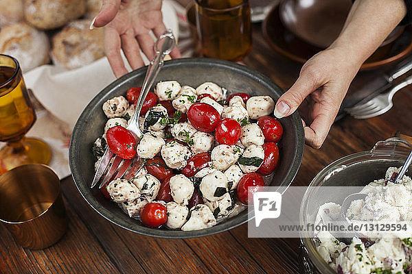 Ausgeschnittenes Bild einer Frau  die am Tisch Tomaten- und Hüttenkäsesalat serviert