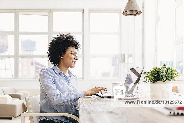Lächelnde Geschäftsfrau mit Laptop-Computer am Schreibtisch im Büro