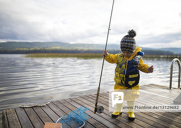 Full length of baby boy wearing raincoat and life jacket while holding fishing rod on wooden pier over lake