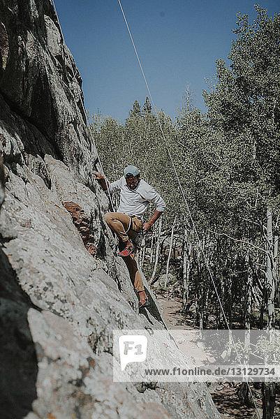 Mann schaut beim Bergsteigen nach unten