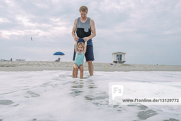 Father and daughter playing in waves at Cape May Beach against sky