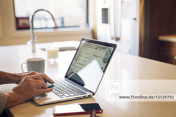 Nahaufnahme einer älteren Frau  die am Laptop tippt  während sie am Küchentisch sitzt