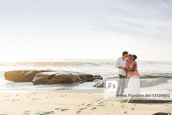 Glückliche Eltern küssen ihre Tochter  während sie am Strand gegen den Himmel stehen