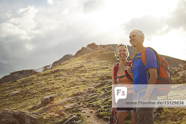 Cheerful couple standing on mountain against cloudy sky