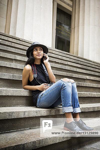Lächelnde Frau spricht am Telefon  während sie auf einer Treppe sitzt