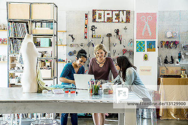 Geschäftsfrauen  die am Laptop im Kreativbüro arbeiten