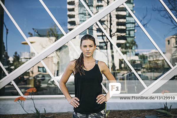 Portrait of confident female athlete standing with hands on hip in city