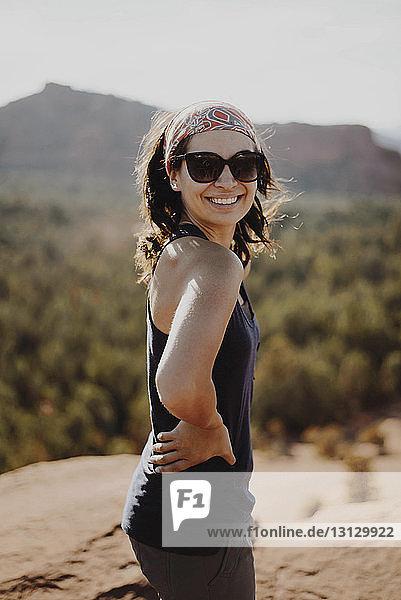 Lächelnde junge Frau steht auf einem Felsen gegen Berge