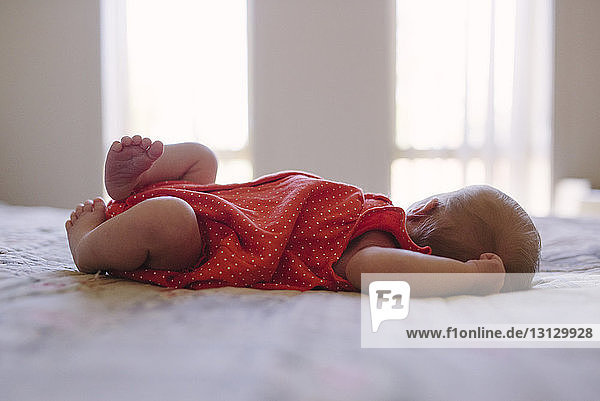 Side view of baby girl relaxing on bed at home