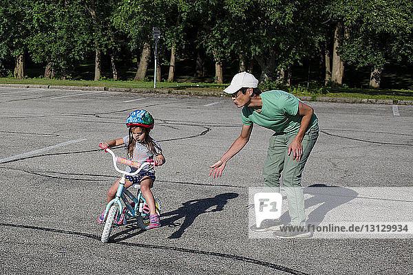 Vater bringt Tochter bei  bei Sonnenschein auf dem Spielplatz Fahrrad zu fahren