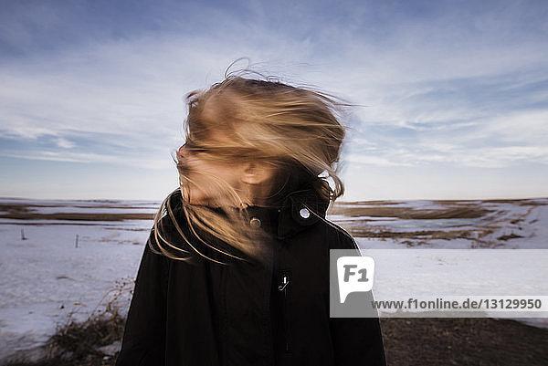 Mädchen wirft die Haare  während sie im Winter auf dem Feld gegen den Himmel steht