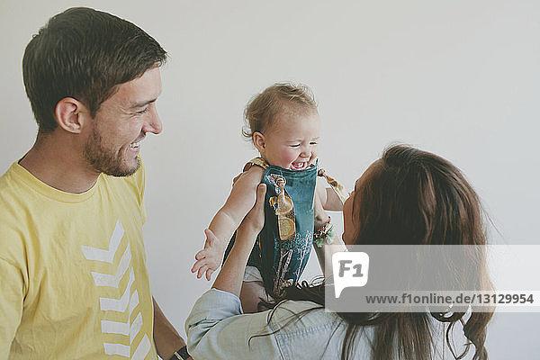 Glückliche Eltern sehen ihre Tochter an  während sie zu Hause an der Wand stehen