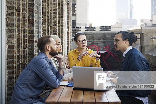 Geschäftsleute diskutieren  während sie auf dem Balkon des Büros sitzen
