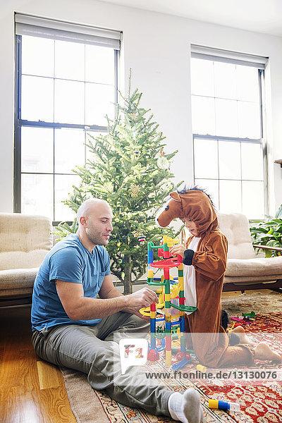 Vater spielt Spielzeugklötze mit dem kostümierten Sohn zu Hause