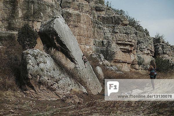 Freunde betrachten den Menschen beim Klettern am Fels im Wald