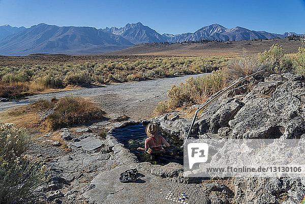 Hochwinkelaufnahme einer Frau in einem Teich bei Felsformationen vor Bergen