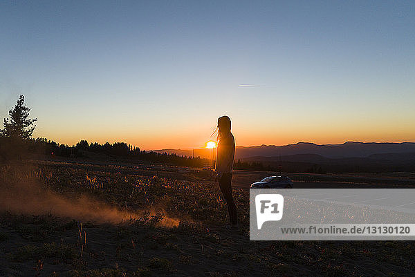 Side view of woman standing on field against sky during sunset