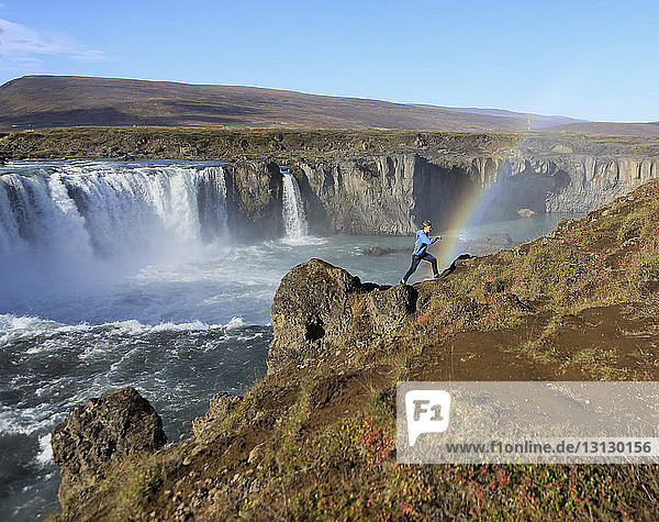 Seitenansicht eines Wanderers  der auf einem Berg gegen Wasserfall und Regenbogen läuft