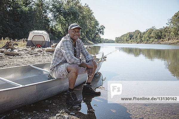Portrait of smiling man sitting on boat at lakeshore