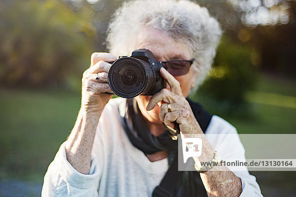 Close-up of senior woman photographing through camera in park