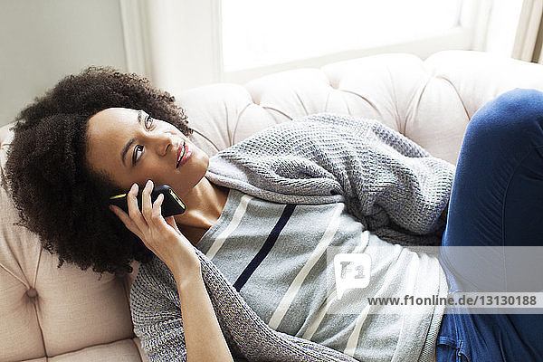 High angle view of woman talking on phone while relaxing at home