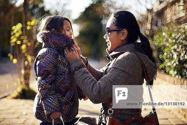 Mutter hilft Tochter beim Tragen des Wintermantels am Fussweg