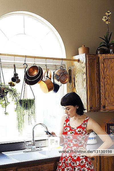 Frau telefoniert  während sie zu Hause an der Küchenspüle steht