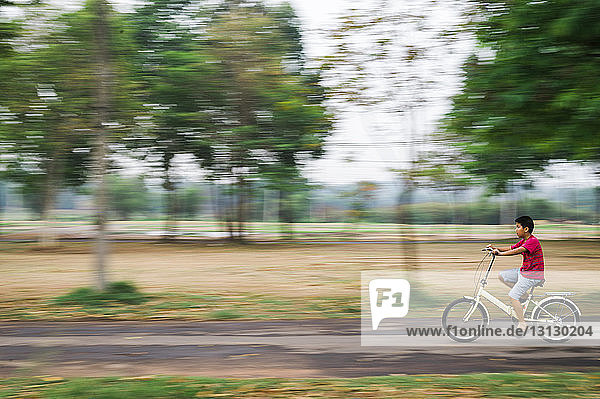 Blurred motion of boy riding bicycle on road at park