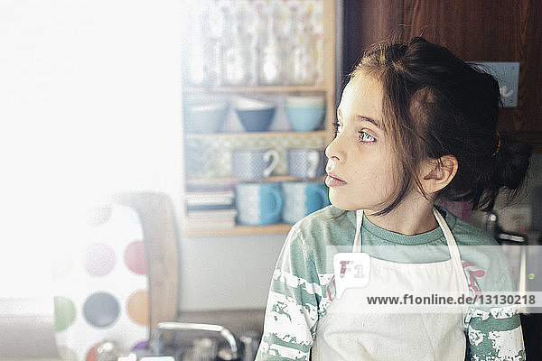 Thoughtful boy wearing apron while looking away in kitchen