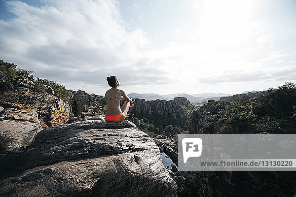 Rückansicht einer Frau im Bikini  die auf dem Berg sitzend gegen den bewölkten Himmel blickt