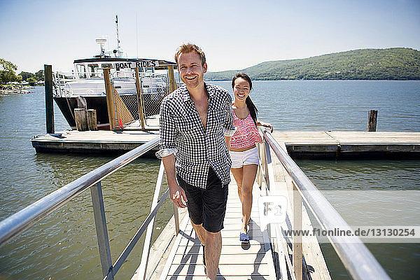 Freunde  die mit einer Yacht über den See gegen den Himmel auf dem Steg spazieren