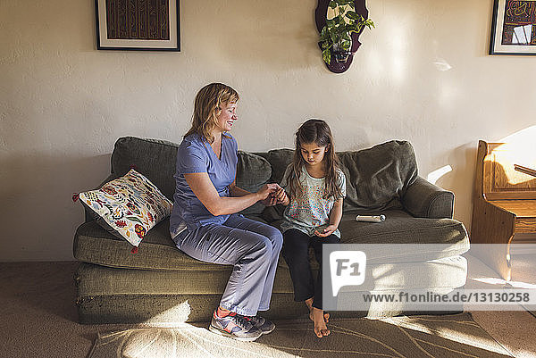 Female doctor with eyes closed checking pulse of girl while sitting on sofa at home