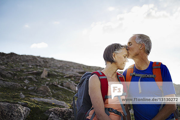 Husband kissing wife on forehead while standing on mountain against sky