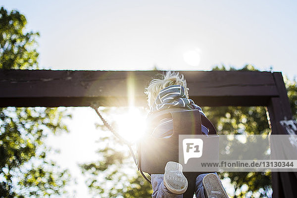 Niedrigwinkelansicht eines Jungen  der an einem sonnigen Tag auf dem Spielplatz schaukelt