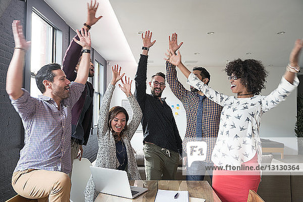 Happy business people with arms raised at desk in office