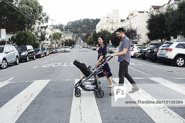 Parents with daughter in baby stroller walking on city street