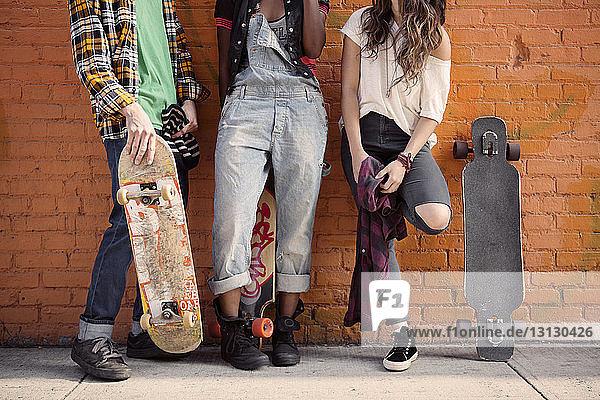 Niedrige Sektion von Freunden  die mit Skateboards an einer Ziegelmauer stehen