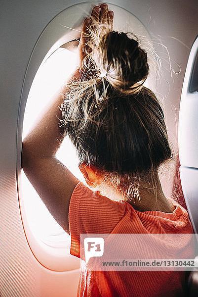 Rückansicht eines Mädchens  das durch ein Flugzeugfenster schaut