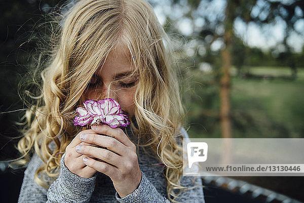 Nahaufnahme eines Mädchens  das an einer Blume riecht