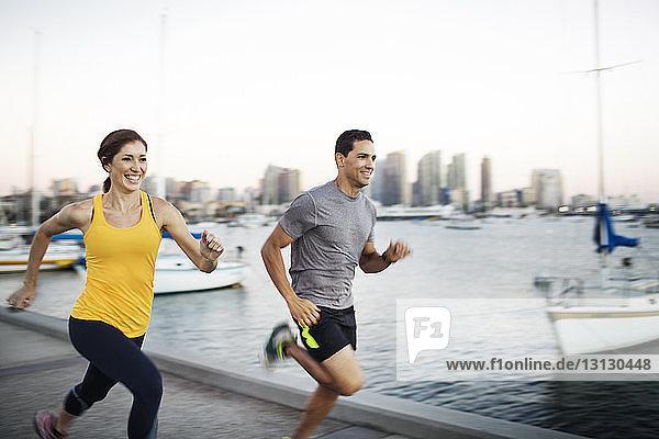Glückliche männliche und weibliche Athleten joggen auf der Mole am Hafen