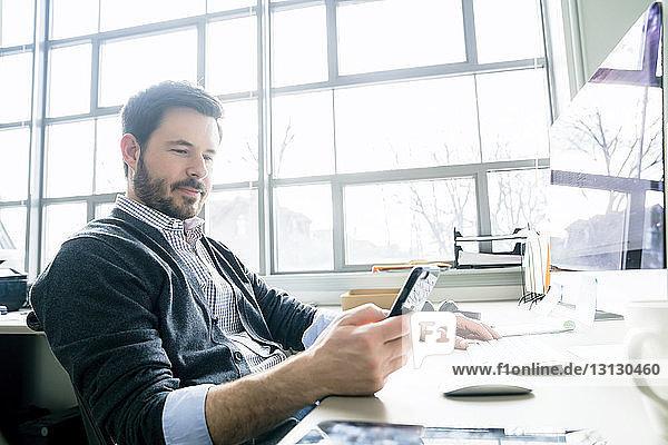 Geschäftsmann benutzt ein Smartphone  während er im Büro am Schreibtisch sitzt