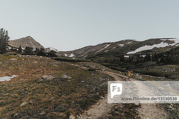 Mid distance view of man walking on trail by mountains against clear sky